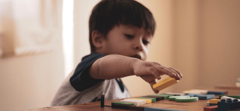 niño con autismo jugando a las fichas en extraescolares en el colegio
