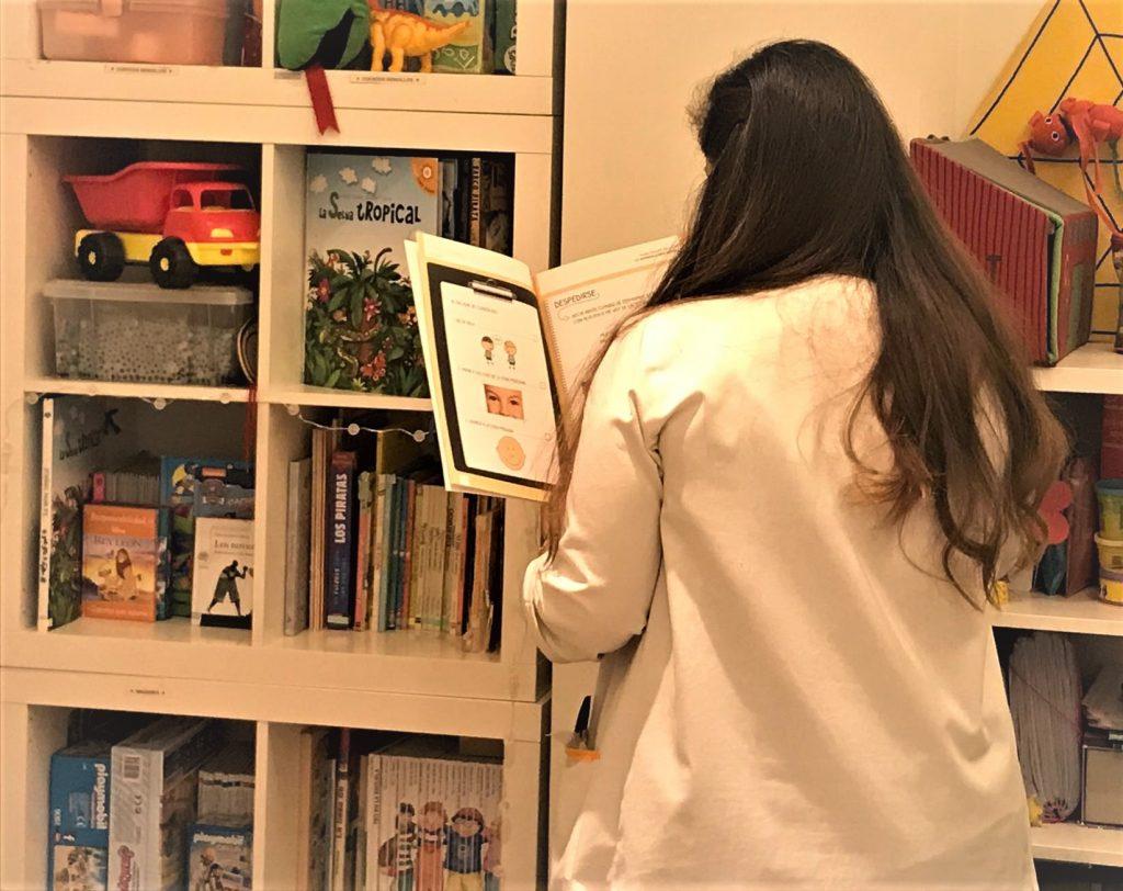 Terapeuta de autista de espaldas leyendo el Diccionario de Habilidades sociales